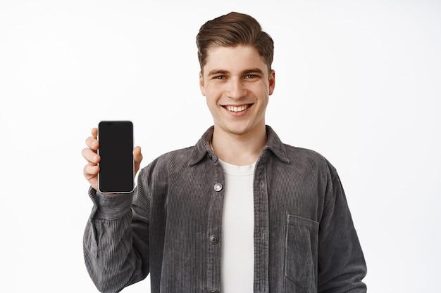 Homem mostra a tela do smartphone, a interface do aplicativo, recomendando o aplicativo, pisando em branco