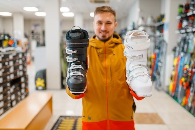 Homem mostra botas de esqui ou snowboard em loja de esportes