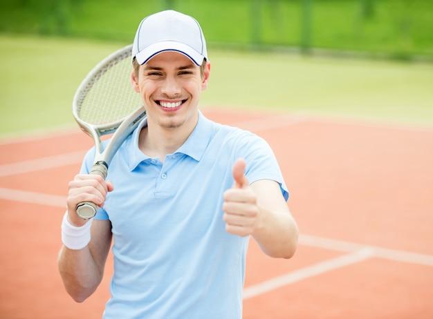 Homem mostra o polegar para cima e detém a raquete de tênis.