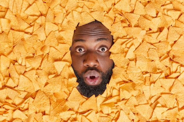 Homem mostra o rosto através de um monte de batatas fritas mexicanas mantém a boca aberta de grande admiração, com uma barba espessa, não consegue acreditar que seus olhos comem um lanche prejudicial à saúde