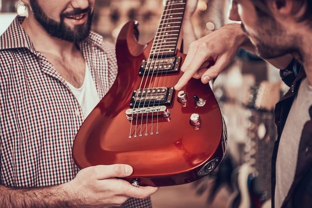 Homem mostra para o comprador onde controle de volume de guitarra.