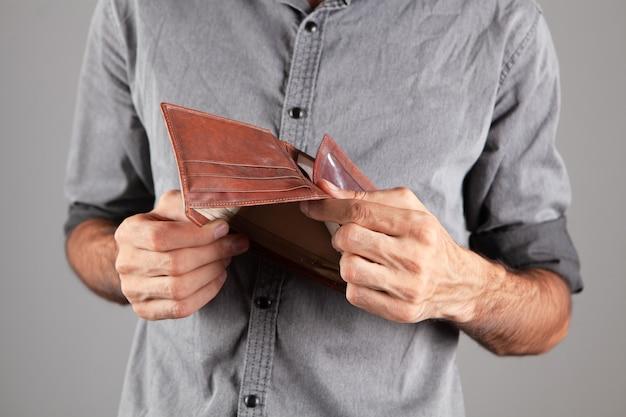 Homem mostra uma carteira de couro vazia.