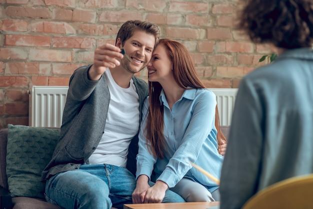 Homem mostrando a chave da nova casa e uma esposa feliz