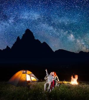 Homem mostrando a mulher para as estrelas no céu