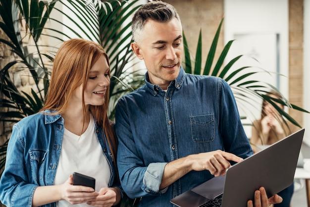 Homem mostrando algo em um laptop para seu colega de trabalho