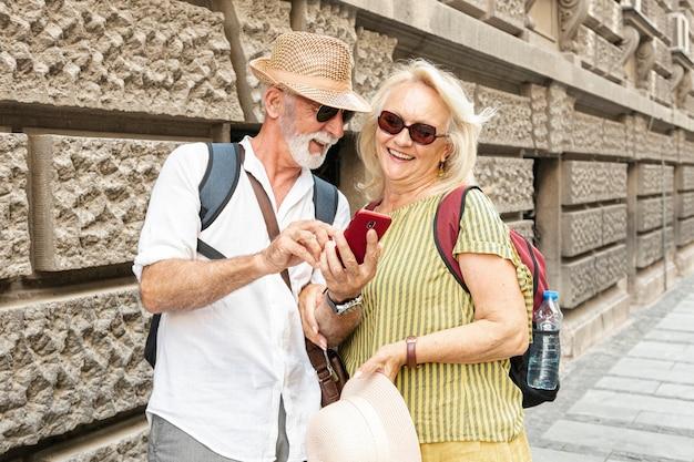 Homem mostrando algo no telefone da mulher enquanto sorrindo