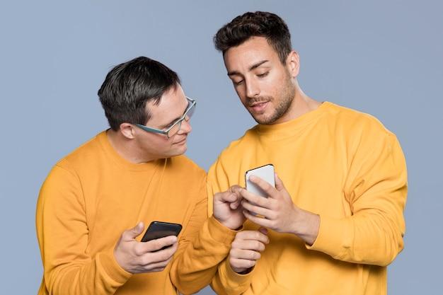 Homem mostrando algo para seu melhor amigo no telefone
