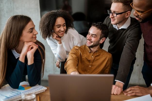 Homem mostrando algo para seus colegas no laptop durante uma reunião