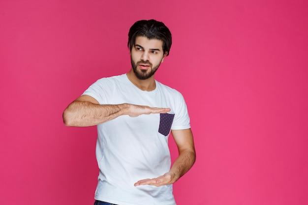 Homem mostrando as dimensões de um pacote com as mãos.