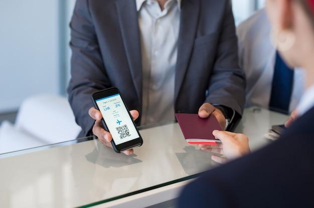 Homem mostrando bilhete de avião eletrônico