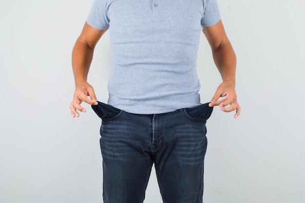Homem mostrando bolsos vazios em camiseta cinza, jeans