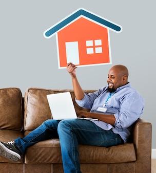 Homem, mostrando, casa, ícone, ligado, sofá