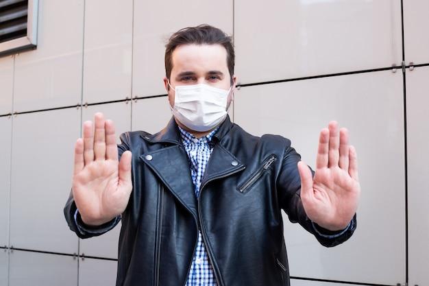 Homem mostrando com as mãos gesto parar. homem usa máscara protetora contra doenças infecciosas e gripe. conceito de cuidados de saúde. quarentena do coronavírus.
