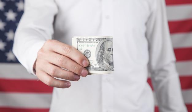 Homem mostrando dólares no fundo da bandeira americana.