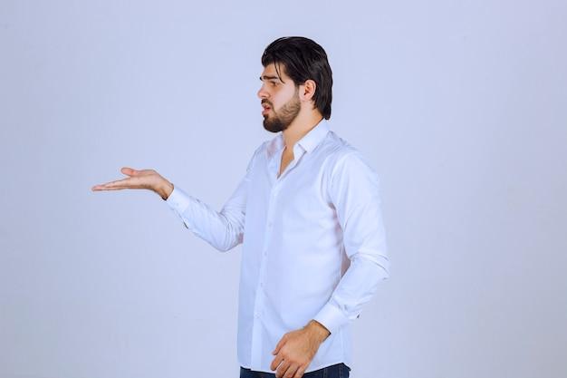 Homem mostrando e apontando para o lado esquerdo.
