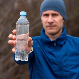 Homem mostrando garrafa de água na natureza