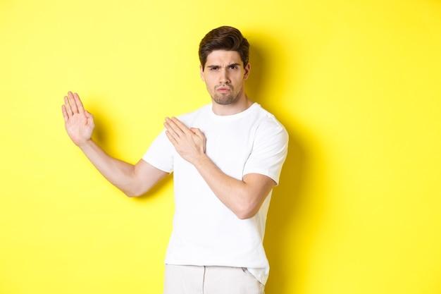 Homem mostrando habilidades de kung-fu, movimento ninja de artes marciais, em pé com uma camiseta branca pronto para lutar, em pé sobre uma parede amarela