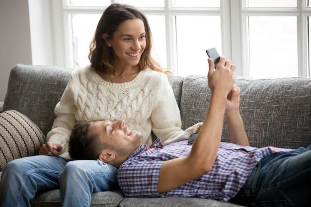 Homem, mostrando, mulher, novo, telefone móvel, app, relaxante, ligado, sofá