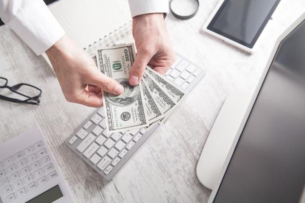 Homem mostrando notas de cem dólares no fundo da mesa de negócios.