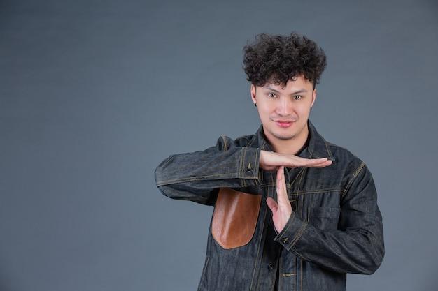 Homem mostrando o gesto com a mão no estúdio por trás posando