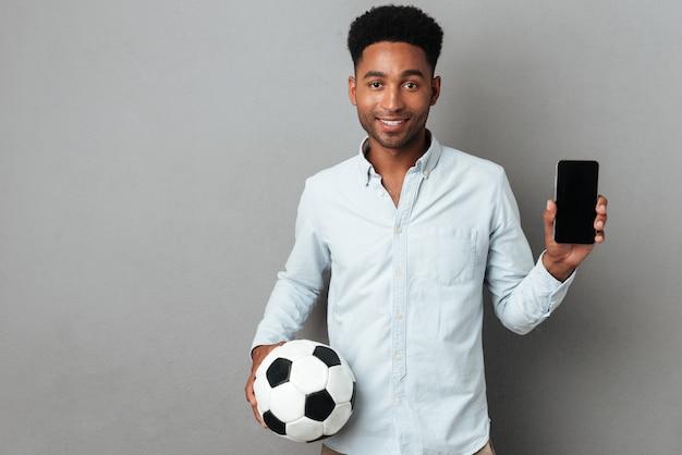 Homem mostrando o telefone móvel de tela em branco e segurando o futebol