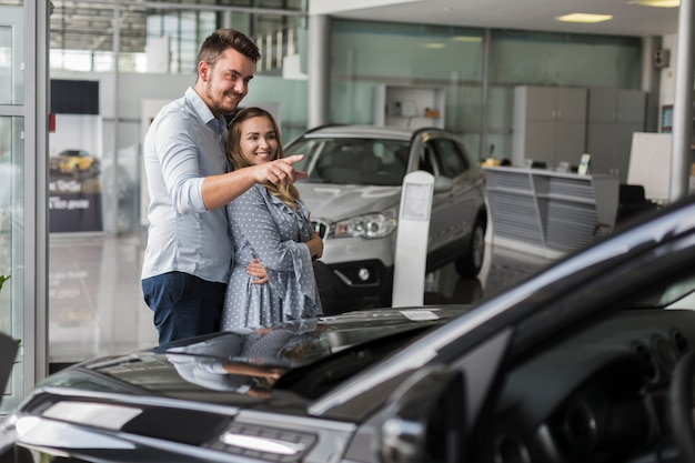 Homem mostrando para sua namorada um carro