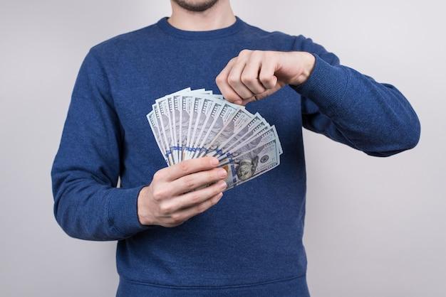 Homem mostrando pilha de dinheiro isolado fundo cinza