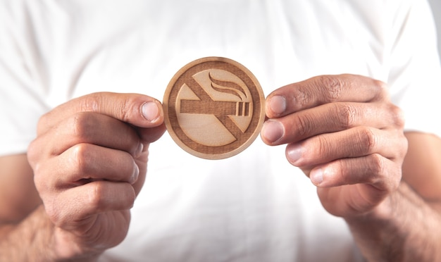 Homem mostrando placa de madeira proibida de fumar
