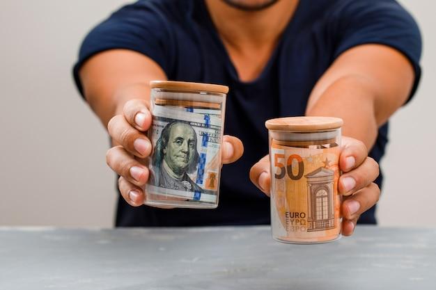 Homem mostrando potes de dinheiro.