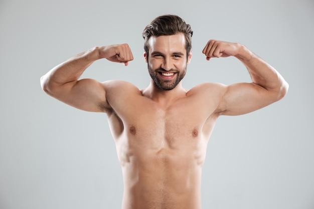 Homem mostrando seu bíceps e olhando para a câmera