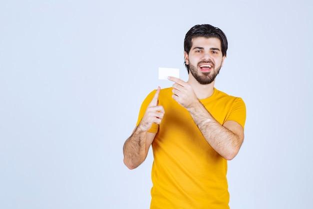 Homem mostrando seu cartão de visita e apresentando-se com confiança.