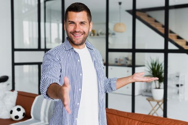 Homem mostrando seus quartos e sorrindo para a câmera