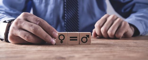 Homem mostrando símbolos masculinos e femininos em cubos de madeira. conceito de igualdade de gênero