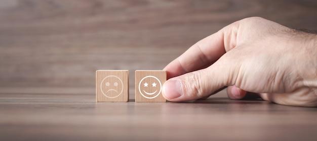 Homem mostrando smileys tristes e felizes em cubo de madeira. satisfação do cliente