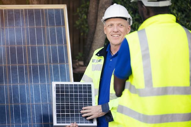 Homem mostrando tecnologia de painéis solares para equipe de engenheiros