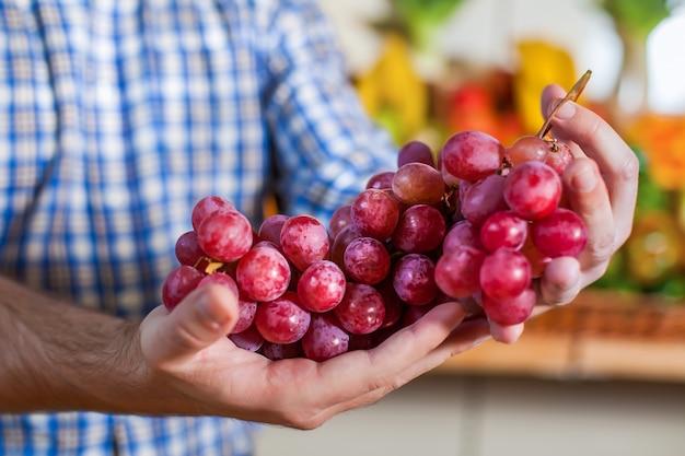 Homem mostrando um cacho de uvas.