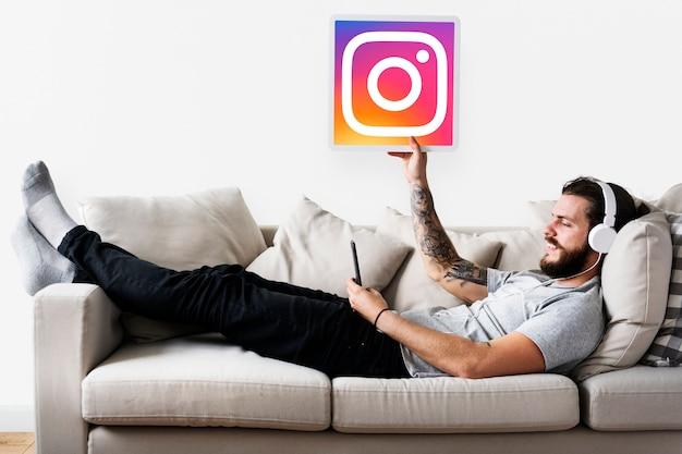 Homem mostrando um ícone do instagram