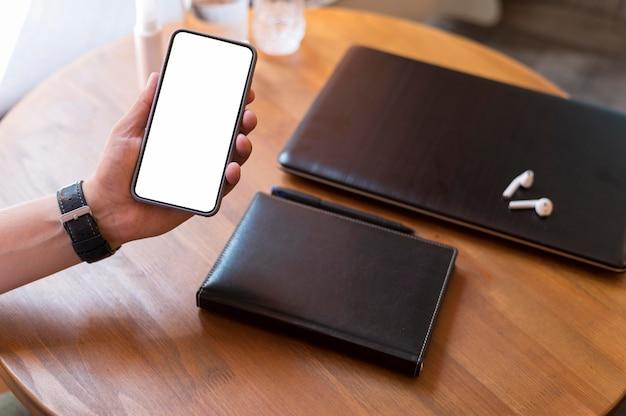 Homem mostrando um telefone com tela vazia