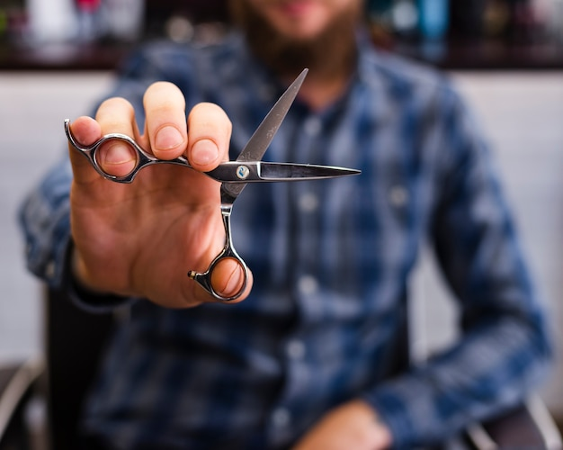 Homem mostrando uma tesoura close-up