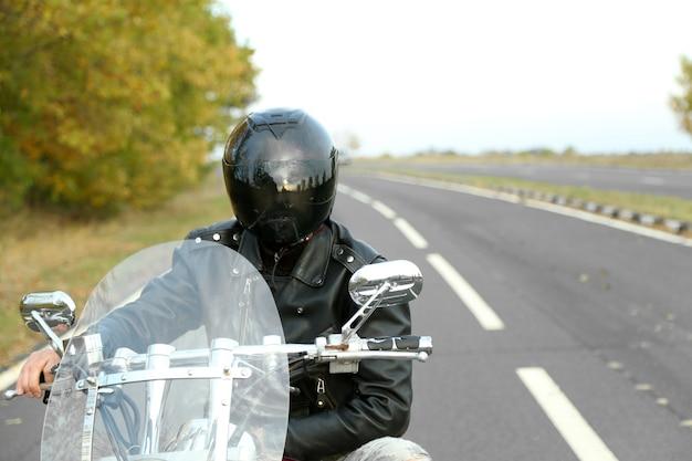 Homem motociclista com capacete preto sentado em uma bicicleta