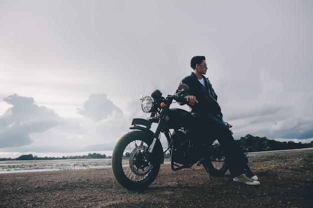 Homem motociclista com sua moto ao lado do lago natural e bonito.