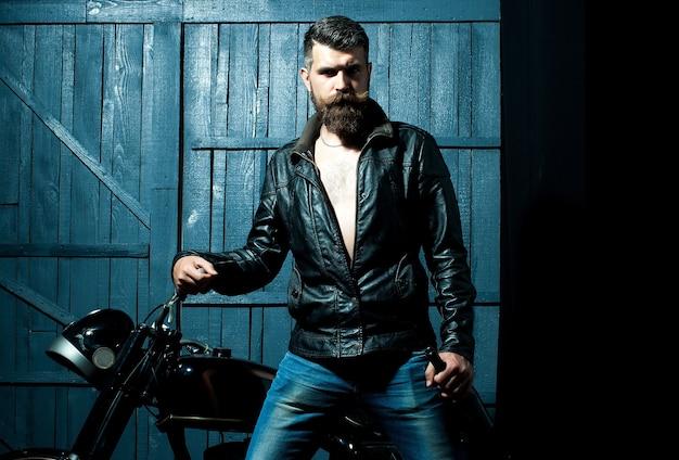Homem motociclista com uma garrafa de vinho perto de moto em um brutal barbudo de madeira