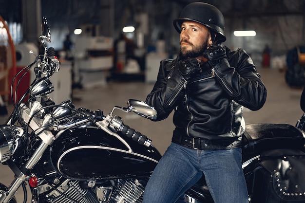 Homem motociclista de jaqueta de couro e capacete, sentado em sua motocicleta