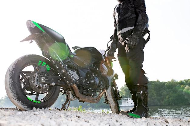 Homem motociclista e motocicleta com espaço no rio, viagem de moto rider na rua à beira do rio, desfrutando de liberdade e estilo de vida ativo.