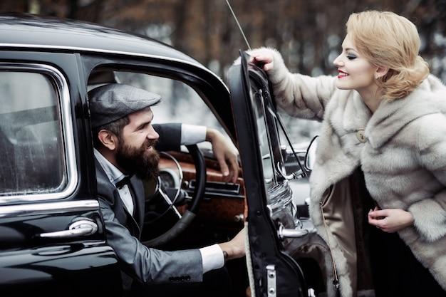 Homem motorista com mulher com casaco de pele casal vintage no carro retrô preto