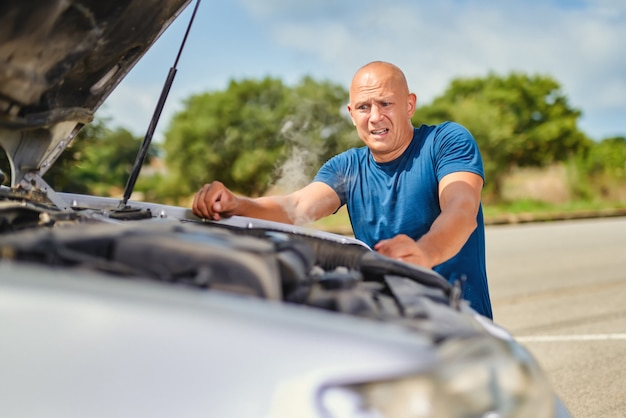 Homem motorista na frente de acidente automobilístico na estrada.