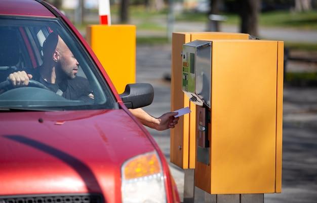 Homem motorista pegando, validar um tíquete na máquina de venda automática para estacionar em área privativa
