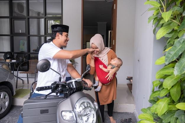 Homem muçulmano andando de scooter deixando sua família para trás em casa