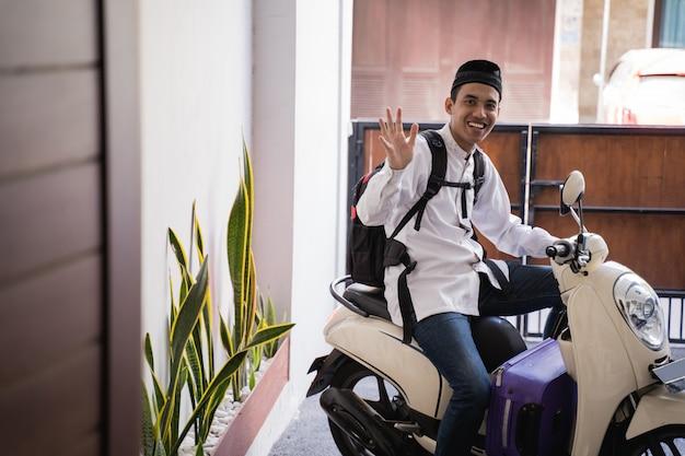 Homem muçulmano andar de moto para idul fitri balik kampung mudik carregando mala
