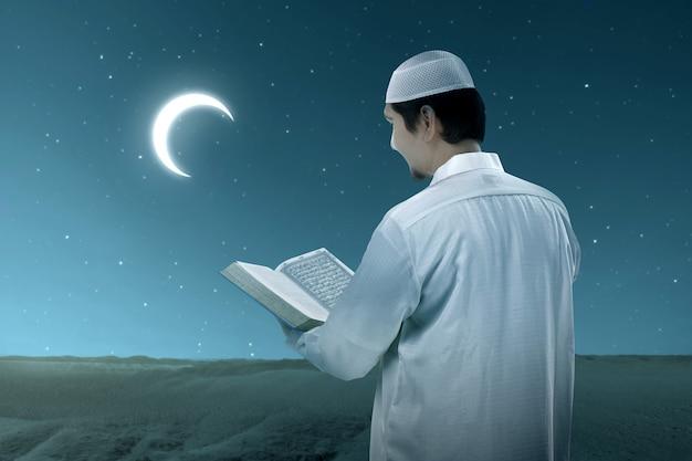 Homem muçulmano asiático de pé e lendo o alcorão com a cena noturna